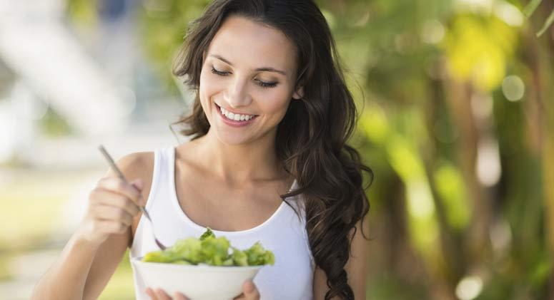 Woman eating a salad outside.
