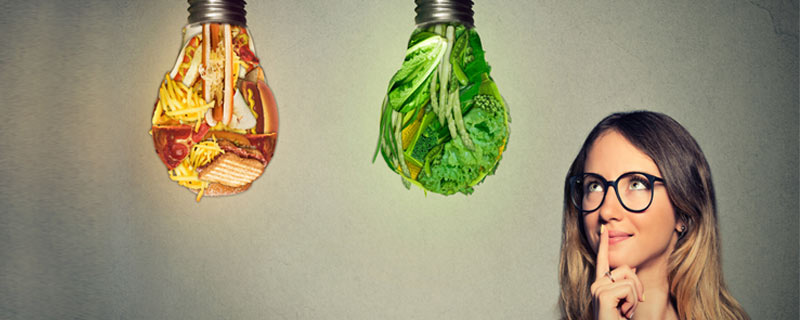 A woman thinking and looking at two lightbulbs. One lightbulb is full of pizza, fries and junk food. Another lightbulb is full of leafy green vegetables.