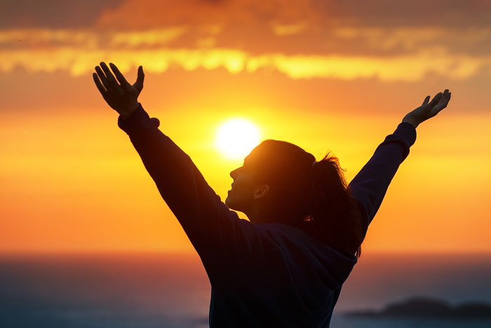 Woman with hands up in the air, sun setting in the background.