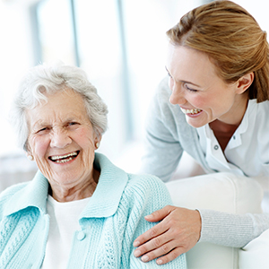A young woman and elderly woman laughing and smiling. Saunas can help reduce the risk of dementia.