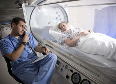 Woman lying in hyperbaric oxygen tank. Male doctor sitting beside her. HBOt helps reverse brain damage.