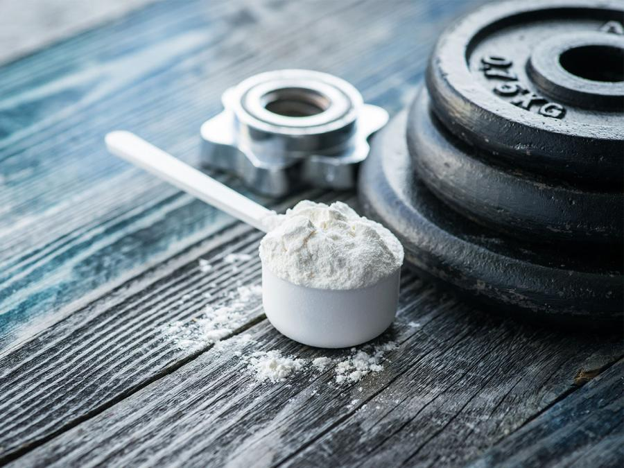 A scoop of creatine powder next to weights. Creatine lowers homocysteine levels.