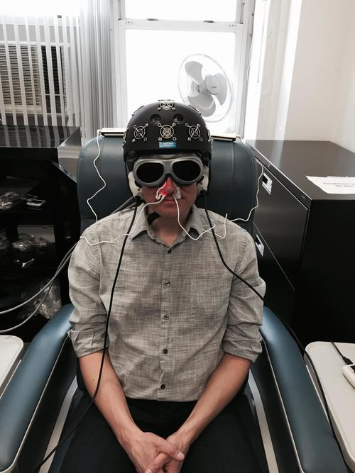 A man wears on LLLT helmet and uses the Vielight intranasal device. LLLT can increase brain blood circulation and increase blood flow to the brain.