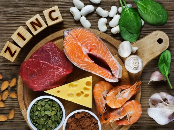 Zinc-rich foods on a table, including salmon, red meat, nuts and seeds. A zinc deficiency can increase anxiety and make you more anxious.