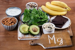A collection of magnesium-rich foods, including avocados, bananas, almonds, dark chocolate, spinach. Magnesium increases oxytocin levels in the brain.