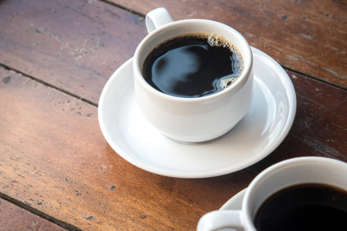 A cup of coffee on a small plate. Coffee and caffeine increases dopamine levels in the brain.
