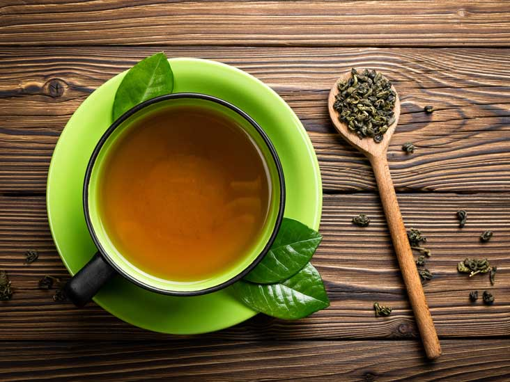 A cup of green tea on a table. And a spoonful of green tea leaves. Green tea can increase dopamine levels in the brain.