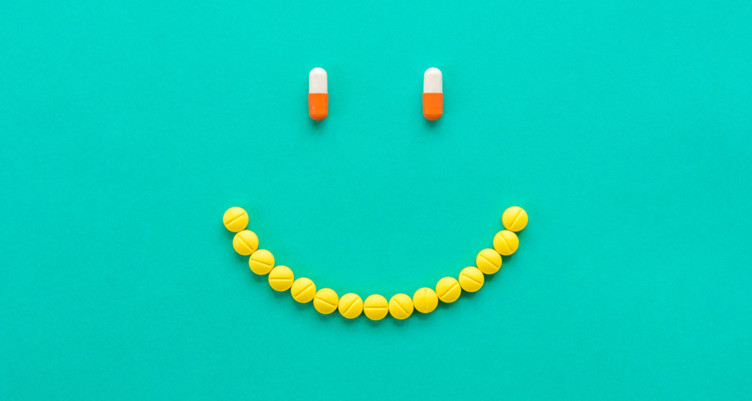A smiley face made out of supplement capsules.