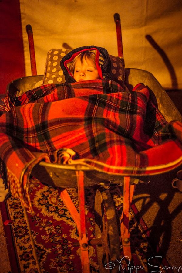 Young child asleep in a wheelbarrow filled with cushions.jpg