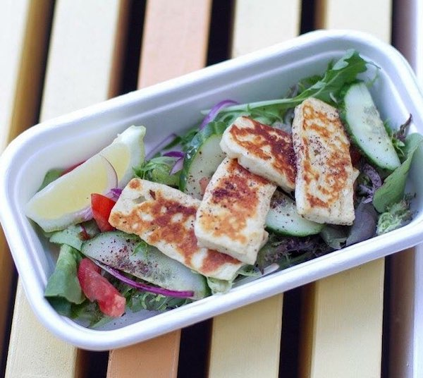 Haloumi salad in a rectangle recyclable container - grilled haloumi on top with cucumber, tomato and a wedge of lemon