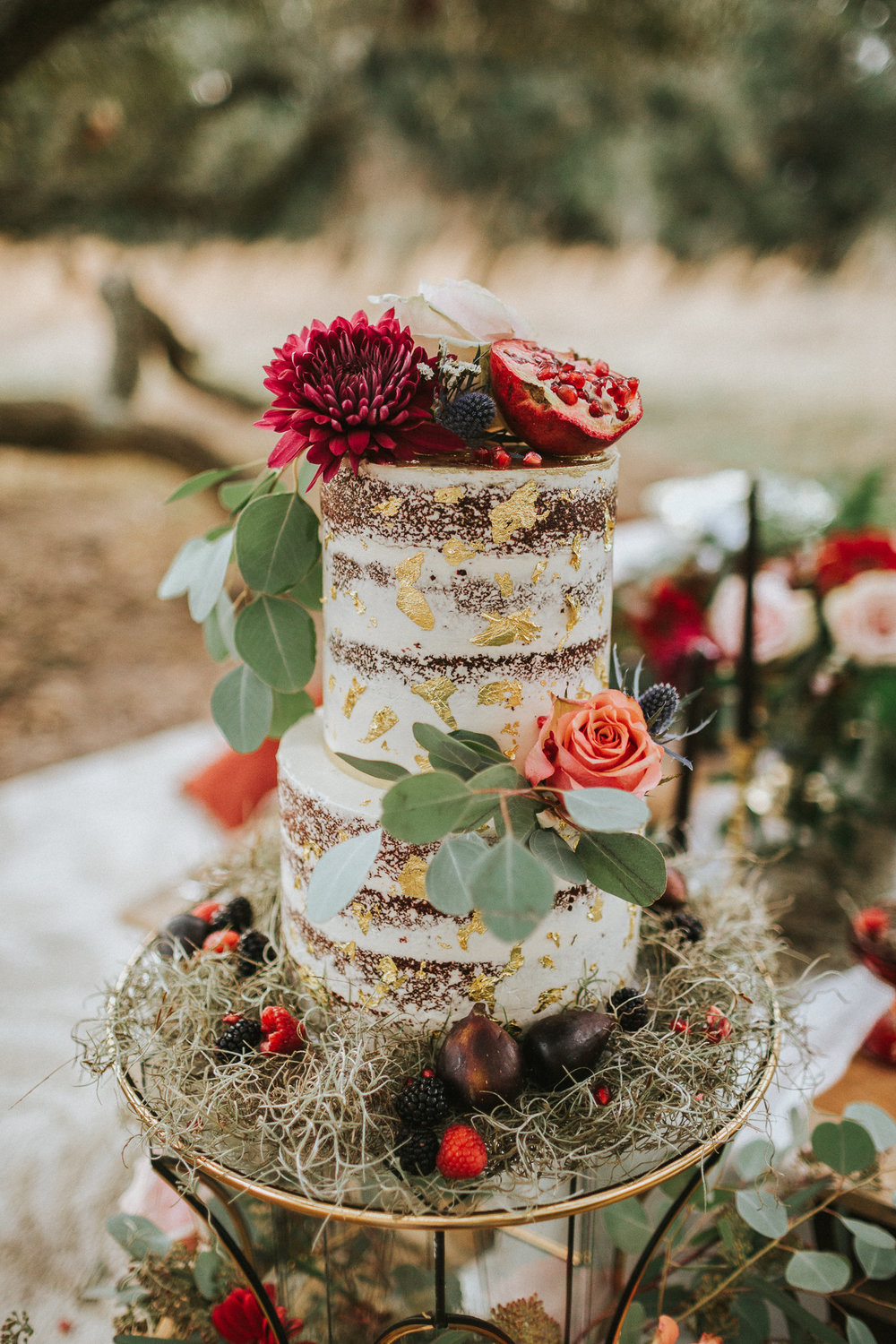 rustic naked cake with red flowers and pomegranate
