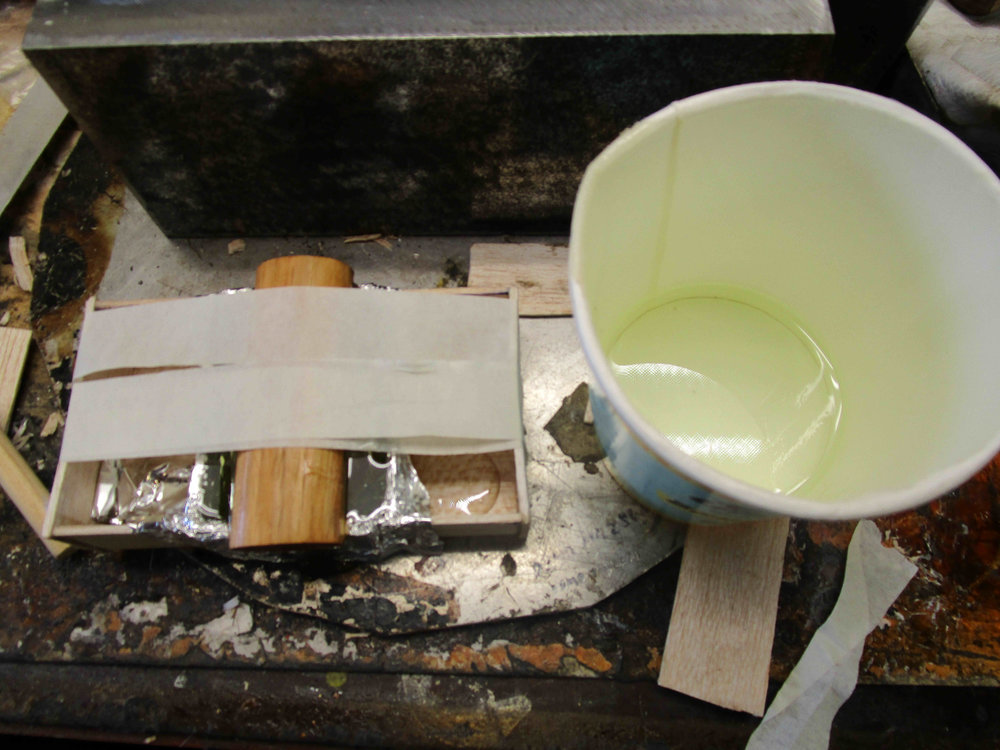 Casting resin pouring box for handle insert. Resin has been poured for the first half. Centre section of box lined with aluminium foil, and sides sealed with blue-tak prior to pouring.