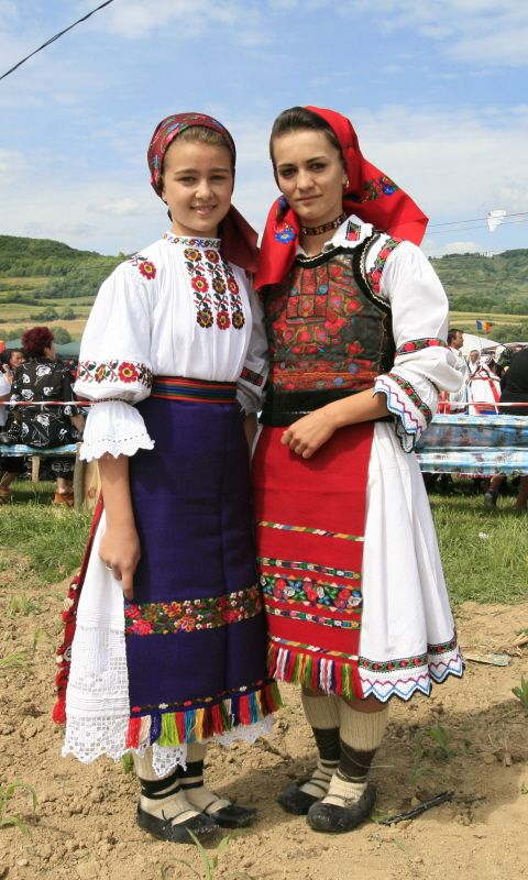 Two beautiful young ladies wearing traditional Romanian dresses. The patterns vary according to region and also family tradition.