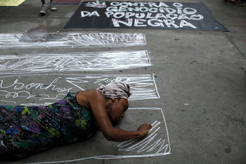 A woman draws pictures of coffins next to a sign condemning the murder of Black youth