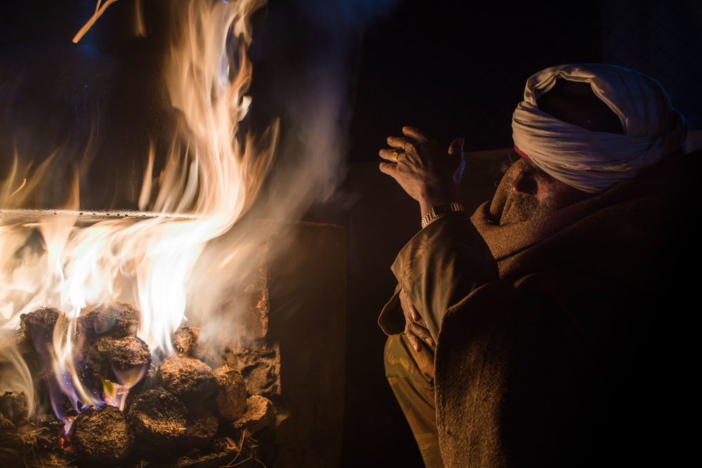 4 am. Manohar lights the fire to cook the porridge for the elephants.
