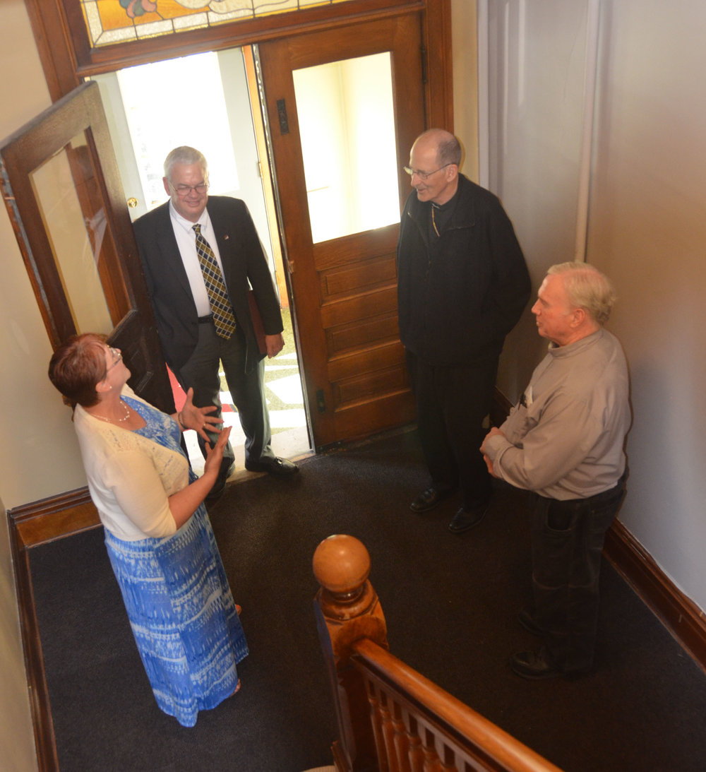 NUMAS Haus Shelter Coordinator Patty Paulson converses in the foyer with Tom Keaveny (left), director of Catholic Charities for the Diocese of New Ulm; Bishop John M. LeVoir; and Deacon Tim Dolan, director of Social Concerns for the diocese and NUMAS Haus board member, during a visit to the house June 21.   (Photo by Christine Clancy)