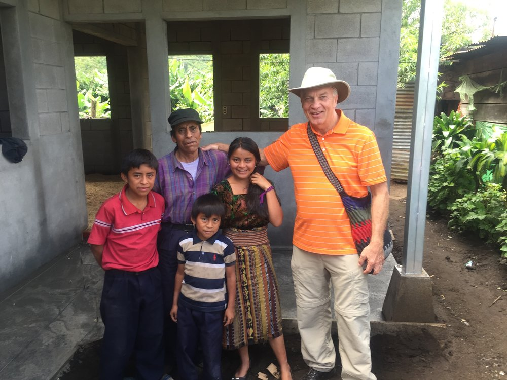 Arch Mrkvicka (right), executive director of the Friends of San Lucas, poses for a photo with Alvaro Archila Subac and three of his four children in front of their new concrete home, which is still being constructed, in San Lucas Toliman, Guatemala. Archila Subac, his wife Rosario Xep Misa, and their family received their new home thanks to generous donations to FOSL.