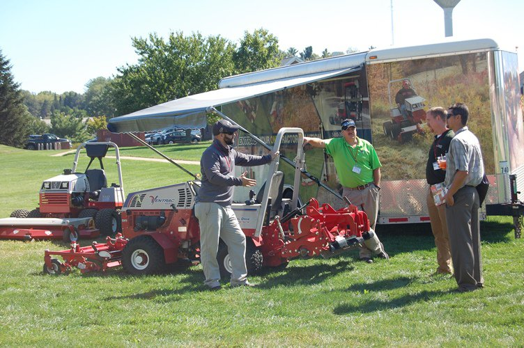 Ventrac employees chat with attendees at their outdoor booth.
