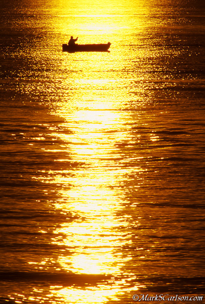 Fisherman in sunset reflection on Lake Superior; ©markscarlson.com