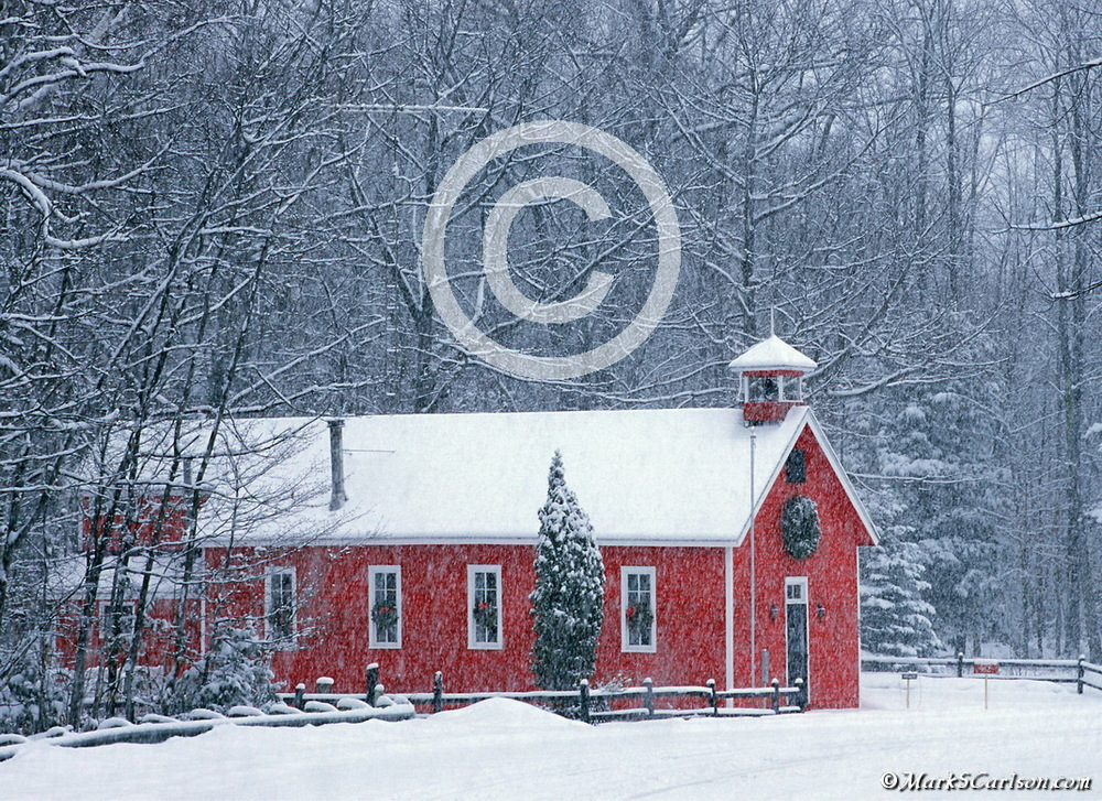 Red schoolhouse with falling snow; ©markscarlson.com