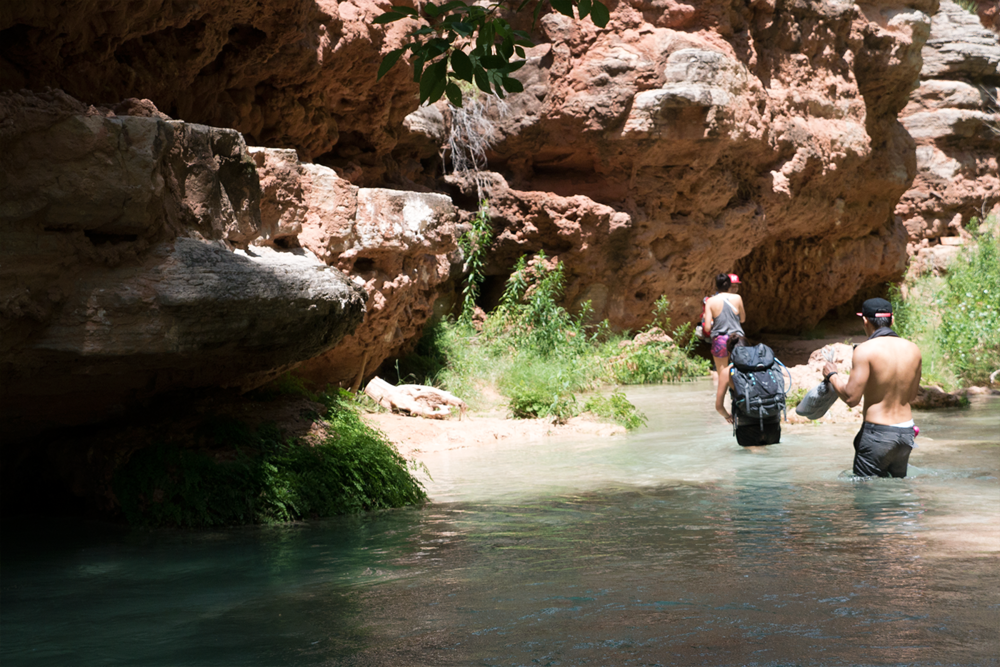 Hoang M Nguyen & Anna Sohee Lee hiking through cool blue streams to Beaver Falls in Havasupai Arizona . Copyright HoboLife