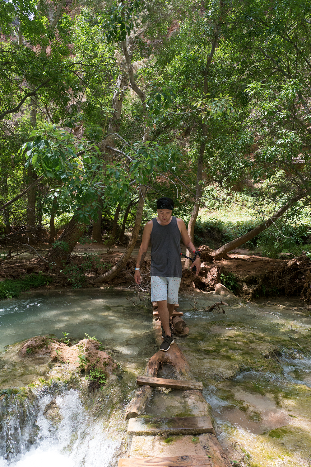 David Vu crossing a small stream in Havasuapi heading to Beaver Falls. Copyright Hobo.Life