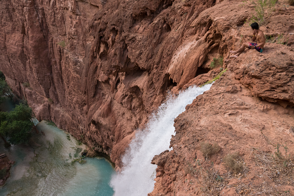 Hoang M Nguyen gazing down 200 ft from the top of Mooney Falls. One of the waterfalls at Havasupai Arizona. Copyright Hobo.Life