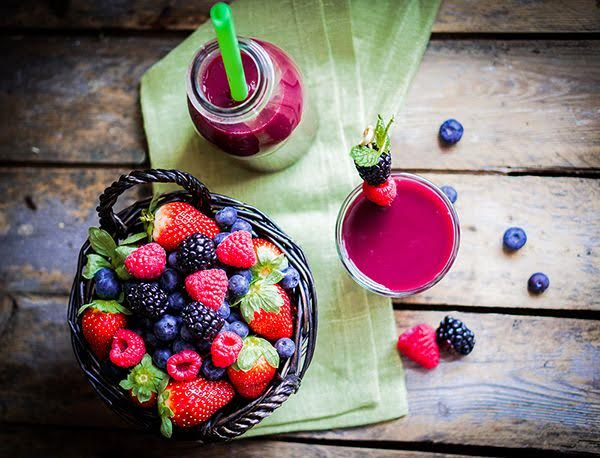 Juice next to blended smoothie with fresh fruit