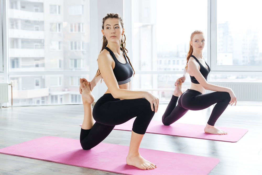 two-beautiful-women-stretching-legs-in-yoga-PGNS87V.jpg