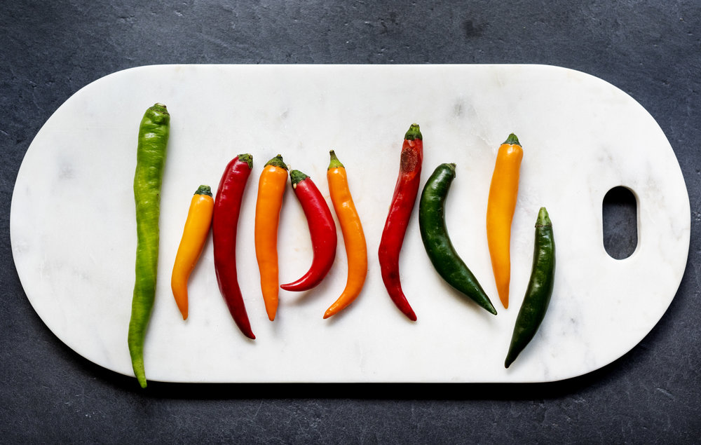 aerial-view-of-cayenne-chili-peppers-on-cutboard-PJC7RKD.jpg