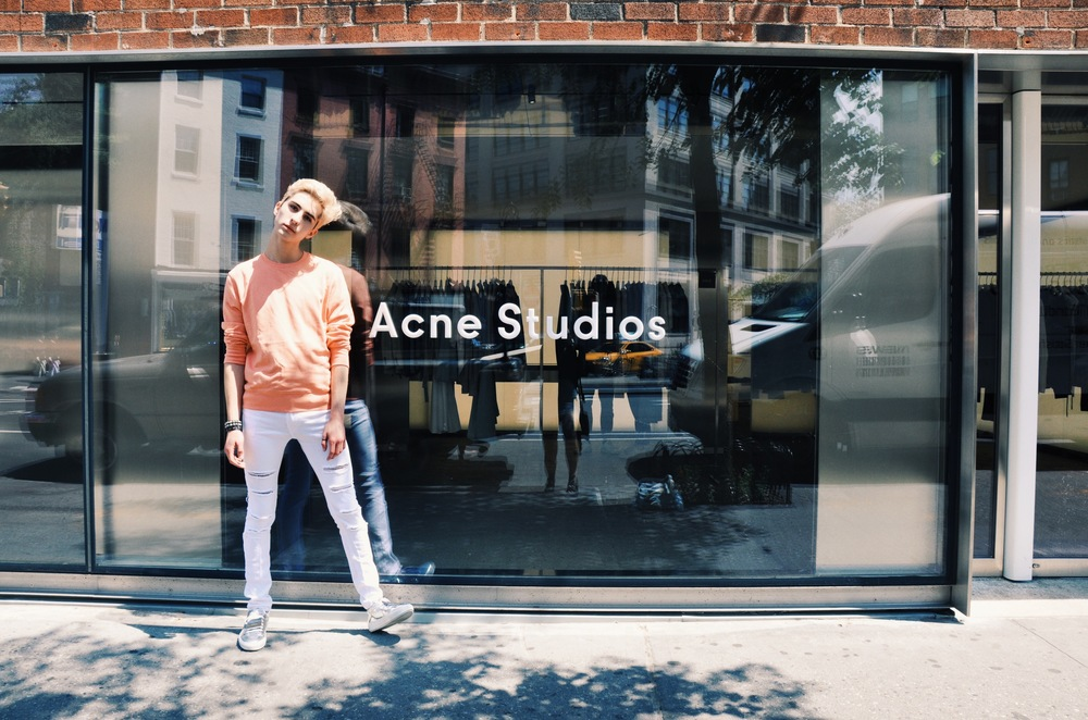 Pictured Above : Ryan Matthew wearing an Acne Studios Coral Melange sweatshirt, H&M white ripped jeans, and Acne Studios Adrian Metal Silver sneakers.