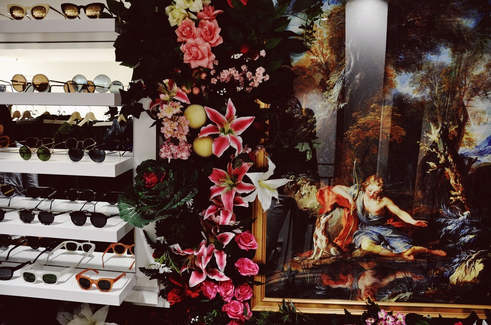 The sunglass collection is integrated into the flower wall on this floor at DSMNY.