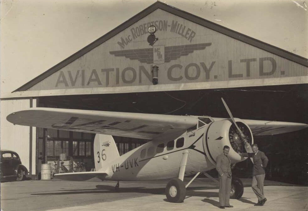 Horrie Miller (right) and Jim Woods standing with MacRobertson Miller Aviation Lockheed DL-1A Vega Special passenger aircraft VH-UVK in front of hangar at Maylands Aerodrome, Perth. (Supplied: National Library of Australia)