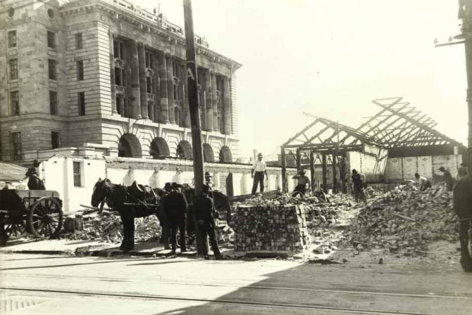 Demolition of the Central Arcade, 1922, with the General Post Office towering overhead. The Central Arcade was said to have been an unhealthy shopping establishment; a view shared by the State Government, which ordered its deconstruction. (Supplied: ABC)