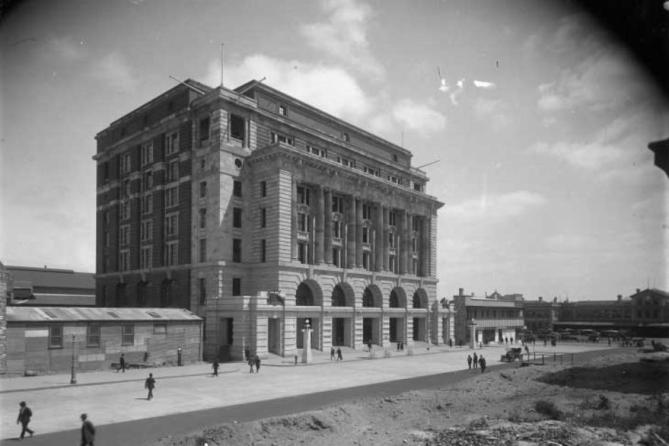 The General Post Office stands as Perth's tallest building as of 1923, with the Central Hotel and Perth Railway Station situated to the right. In the foreground, the Central Arcade has been demolished and construction of the new roadway will be complete by the end of the year. The General Post Office began construction on 8 October 1915, due to the need of a larger space for the Commonwealth Government offices, and was officially opened 26 September 1923. The new road in front of the building was opened the same day, and was named for Sir John Forrest, Western Australia's first Premier.