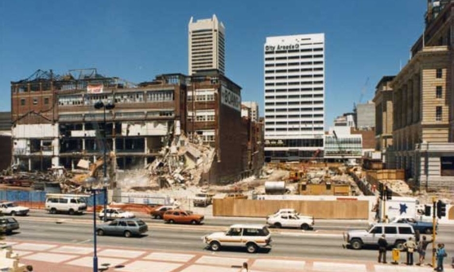 Redevelopment of Forrest Place roadway into a pedestrian plaza, 1987, with the deconstruction of the Boans Building on the left. The Padbury Buildings have been completely demolished in the centre, with the road itself being repaved and widened to encompass the whole width of the plaza. (Supplied: ABC)