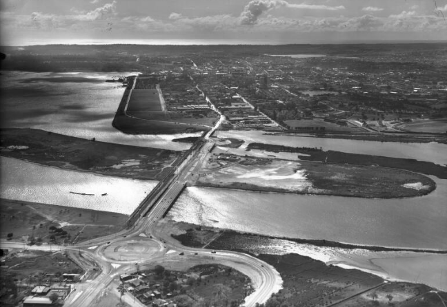 The third Causeway under construction in 1951, with the second causeway still standing to the left. Clearly visible, the eastern roundabout is taking shape but the western won't be built for another two years. (Supplied: National Library of Australia)