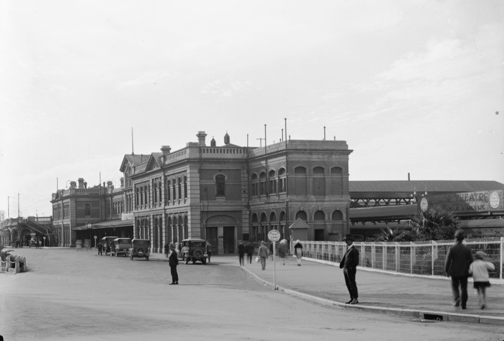 Perth Railway Station was designed by Government Architect George Temple-Poole in the neoclassical style of which his works in Western Australia are famous for. The new station was built in the large space between Perth Central Station, and Wellington Street, allowing the old station to remain in operation throughout construction, which was complete by 1893. The new building was significantly larger than the original, with ticketing offices, waiting rooms, a refreshment room, and several offices downstairs, with the offices of the Western Australian Government Railways headquartered in the second level. The old Central Station was then demolished and the space in which it resided became additional island platforms for the growing number of interstate and commuter services. Pictured, Perth Railway Station in 1927, looking west down Wellington Street. A train is waiting at a platform to the right, and an advertisement for a local theatre can be seen attached to the platform roof. (Supplied: State Library of Western Australia)
