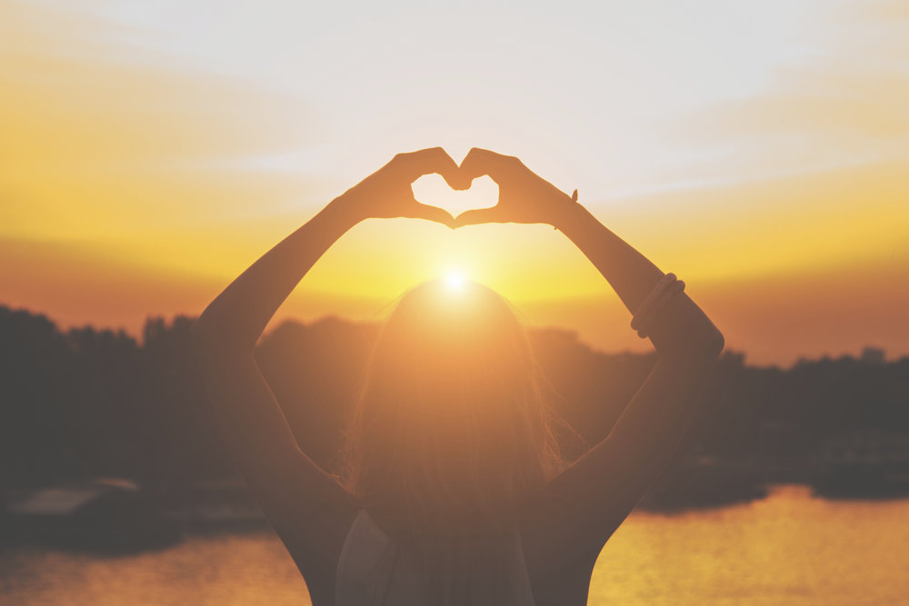 Woman Forming a Heart With Her Fingers In Sunset