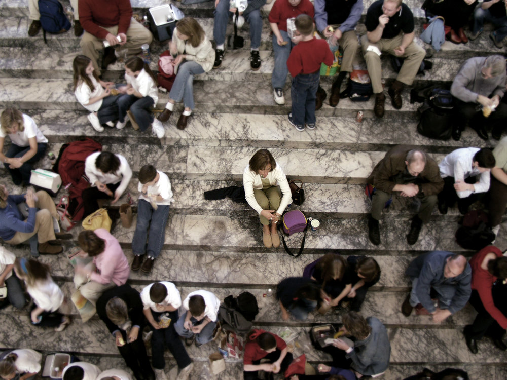Image description: An outdoor scene on crowded marble staircase. Various people are seated across the large staircase, but in the center, isolated from the other people and surrounded by a wide circle of space, sits one solitary person.