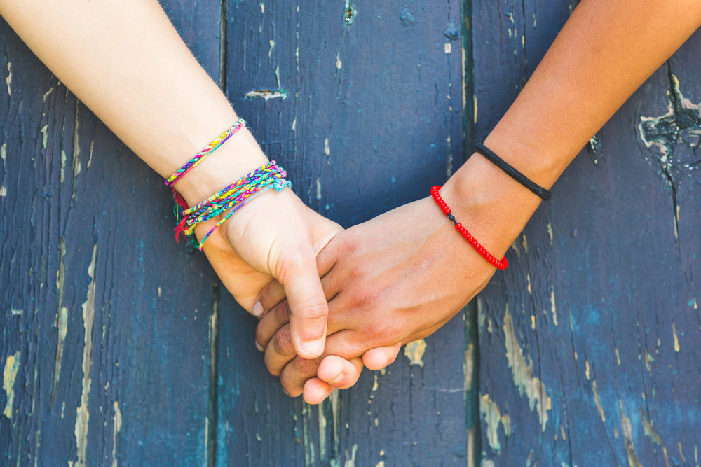 Image description: On a wooden background that is painted a chipped blue, two arms reach across and grasp hands. The left arm is a light skinned person wearing multiple rainbow colored friendship bracelets. The right arm is a brown skinned person wearing a red bracelet and a black bracelet that may be a hair-tie rubber band.