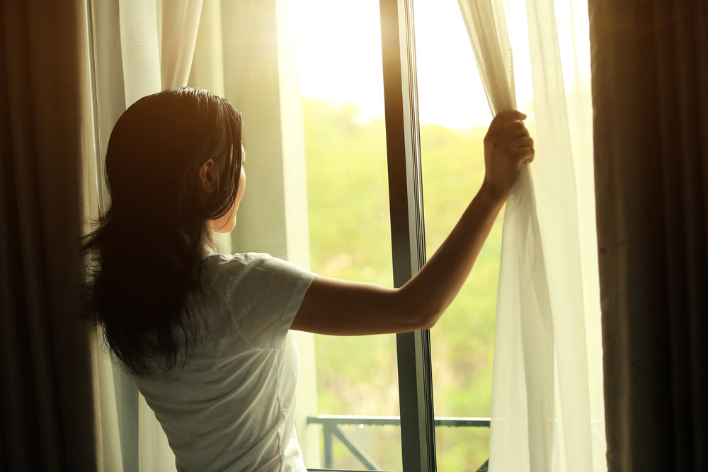 Image: Asian woman parting curtains to look out a sunny window