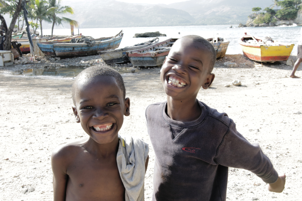 TWO YOUNG BOYS PLAYING ON THE SANDY SHORES IN JACMEL, SOUTHERN HAITI.