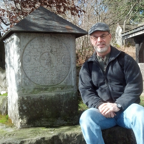 Dr. Mark Winborn next to the square stone that Jung carved at Bollingen.
