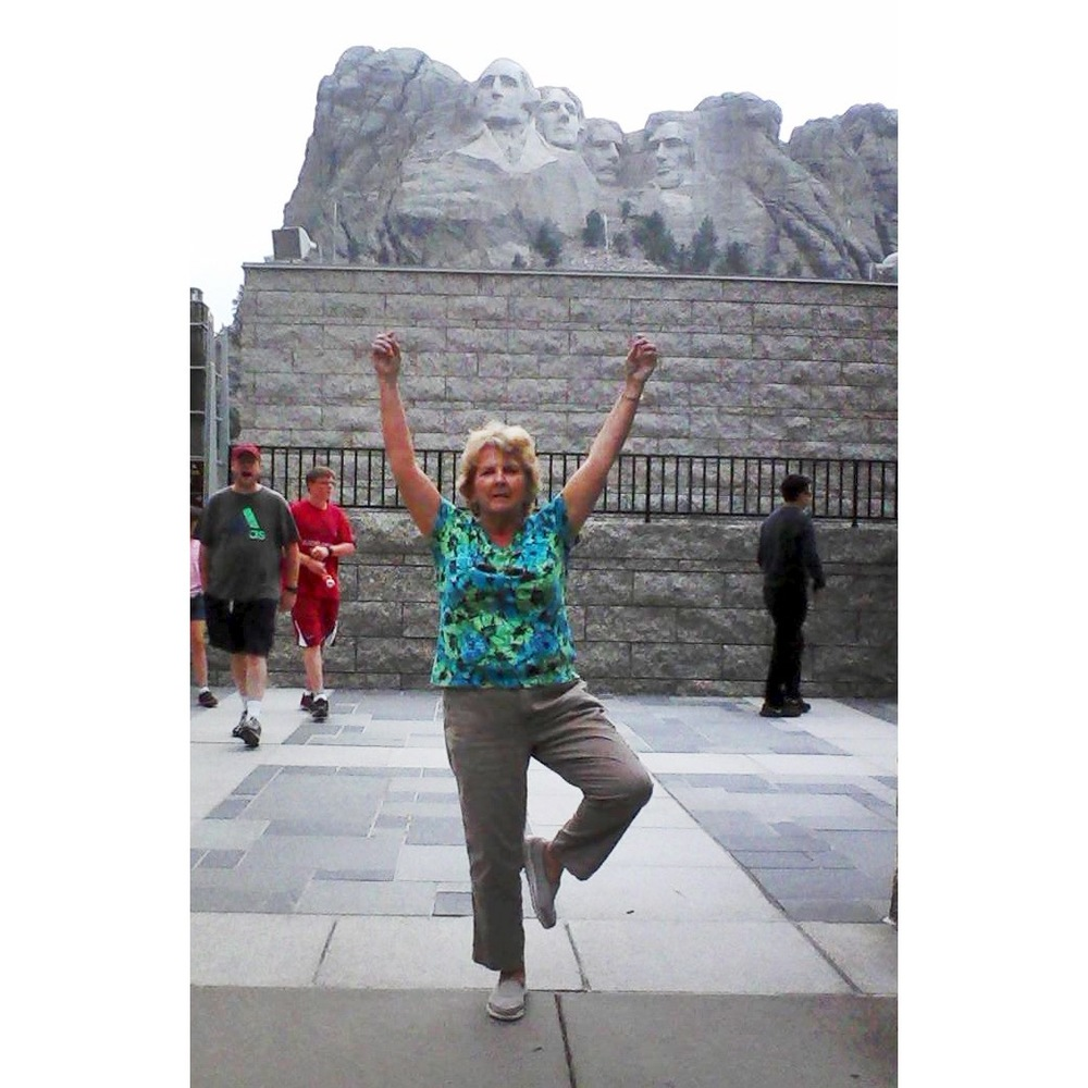 Yoga student Sandy in Tree pose at Mount Rushmore