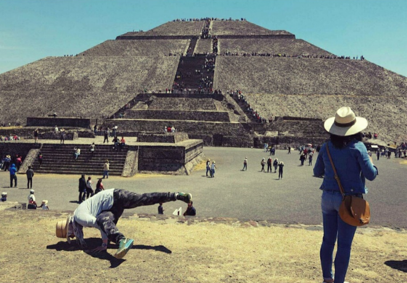 Yoga student Laila, in Side Crow pose in front of the Pyramid of the Sun in Mexico