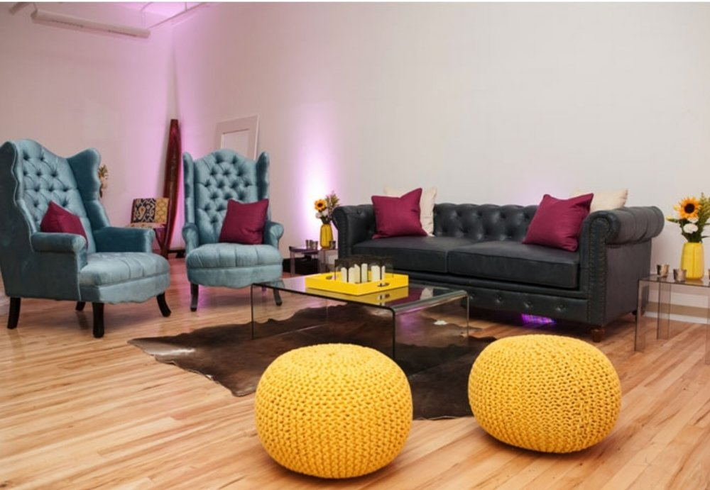 PICTURED: Blue Chesterfield Sofa,  Madison Velvet Armchair, Peekaboo Coffee Table, Yellow Knitted Pouf, Cowhide Throw Rug