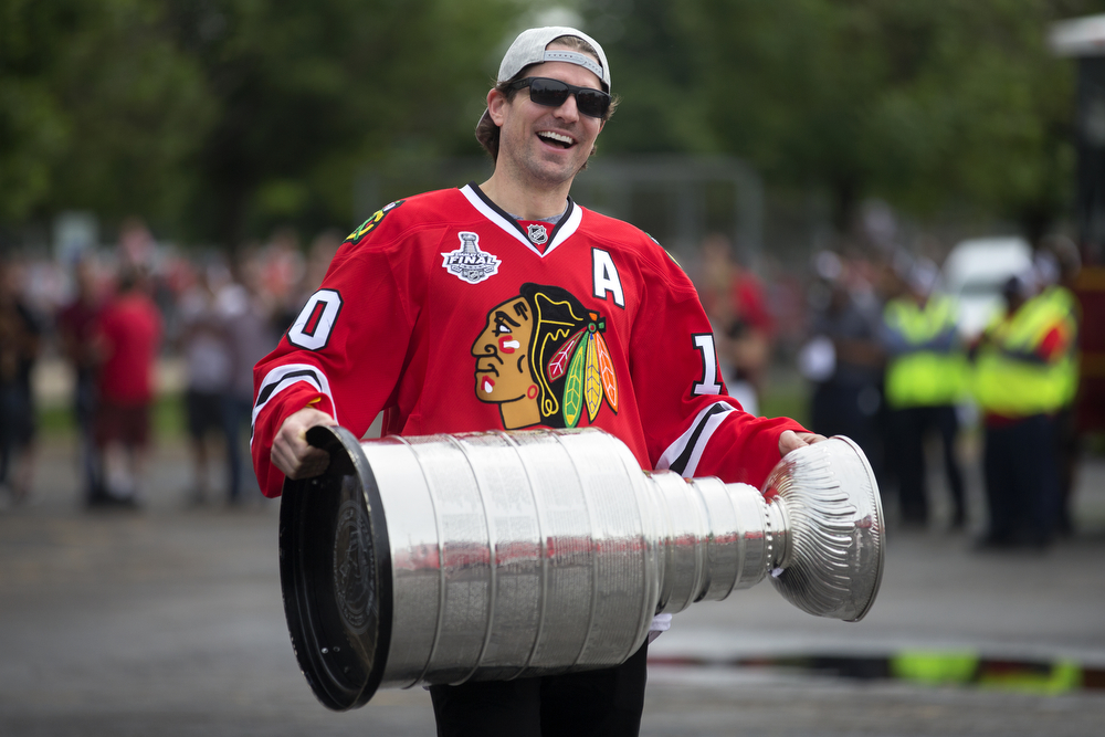 A clean-shaven Patrick Sharp carries the Stanley Cup to a bus at the United Center in Chicago for the start of the championship parade on June 18, 2015. (Erin Hooley/Chicago Tribune)