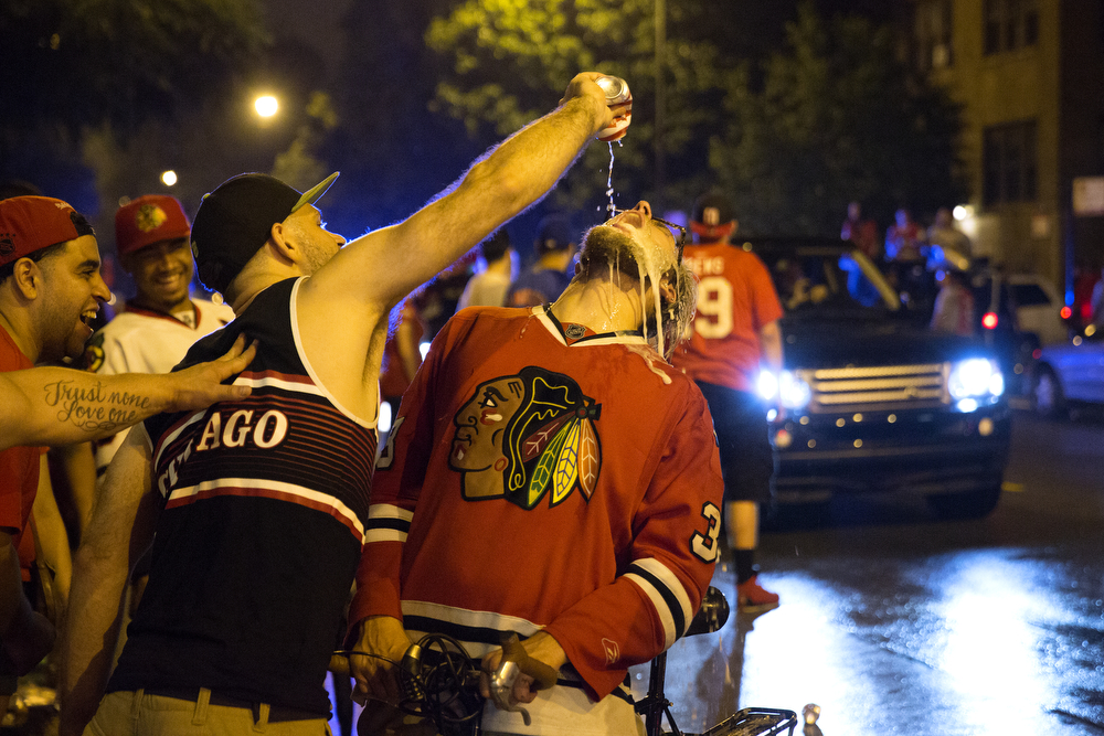 A man pours beer into another man's mouth as fans celebrate the Chicago Blackhawks' Stanley Cup win over the Tampa Bay Lightning in Wrigleyville Monday, June 15, 2015. (Erin Hooley/Chicago Tribune)