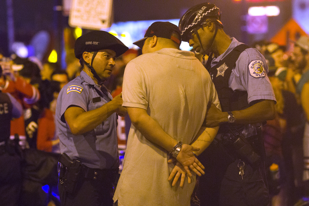 Police officers talk to a man in hand cuffs as fans celebrate the Chicago Blackhawks' Stanley Cup win over the Tampa Bay Lightning in Wrigleyville Monday, June 15, 2015. (Erin Hooley/Chicago Tribune)